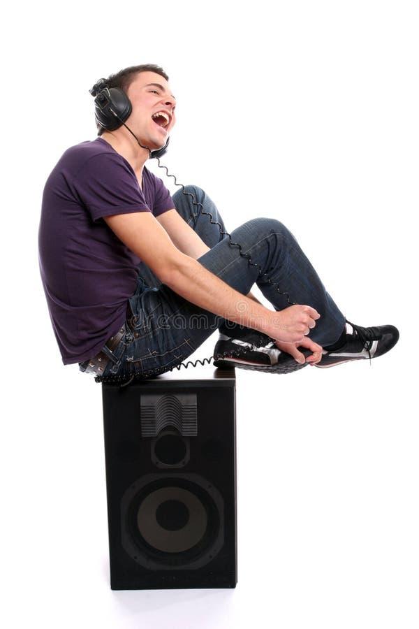 Junger beiläufiger Mann, der Musik hört stockfotografie