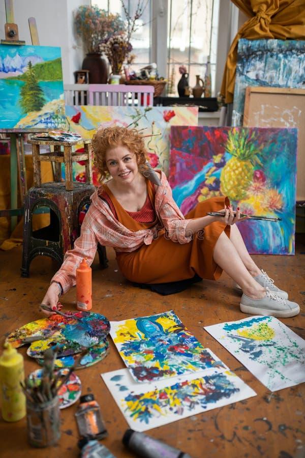 Junger berühmter Künstler, der auf Boden nahe ihren Bildern sitzt lizenzfreie stockfotografie