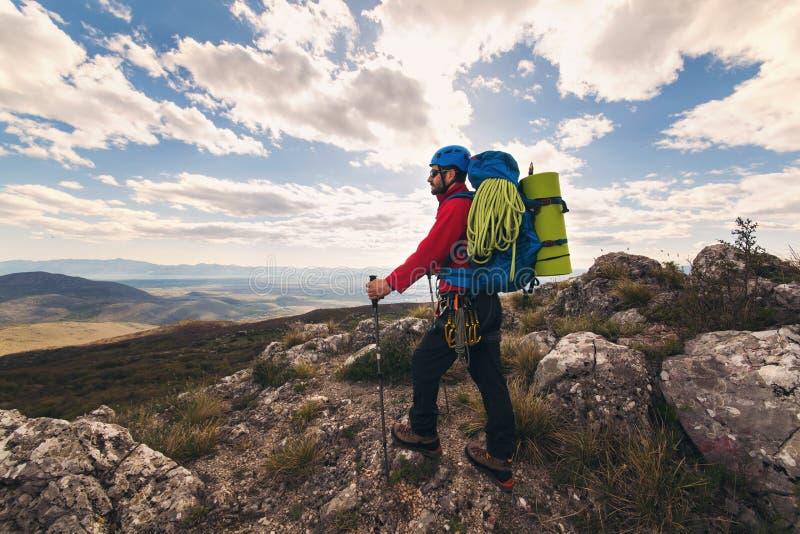 Junger Bergsteiger, der mit Rucksack auf einen Berg steht lizenzfreies stockfoto