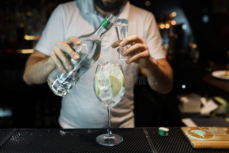 Junger Berufsbarmixer gießt Alkohol von einer Flasche in ein Glas an einem Nachtklub oder an einer Bar Kochen des köstlichen ursp stockbild