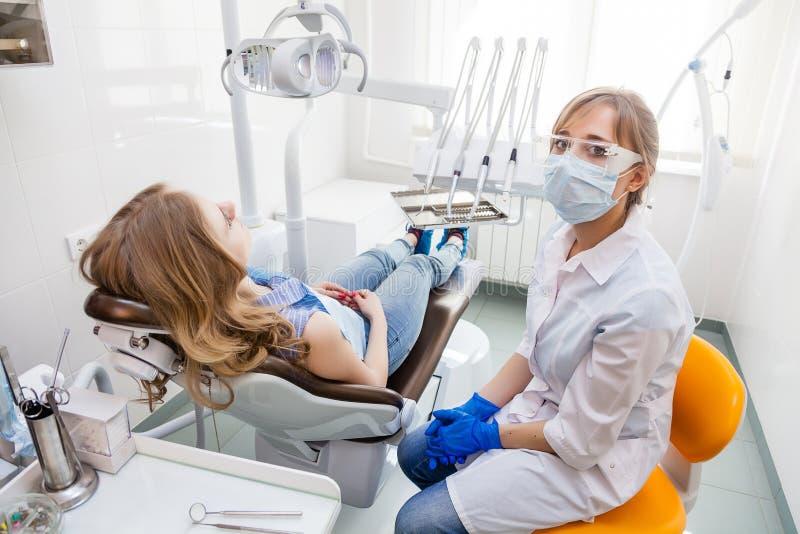 Junger Berufsfrauen-Zahnarzt und ihr Patient stockbild