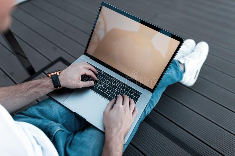 Junger Berufsgeschäftsmann benutzt einen Laptop für Arbeit Bloggerkerl arbeitet an einem Computer Draufsicht über männliche Hände stockfoto