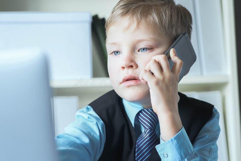 Junger ?berzeugter Exekutivgesch?ftsmannchefjunge in den B?rogespr?chen am Telefon, das am Schreibtisch mit Laptop sitzt stockfotos