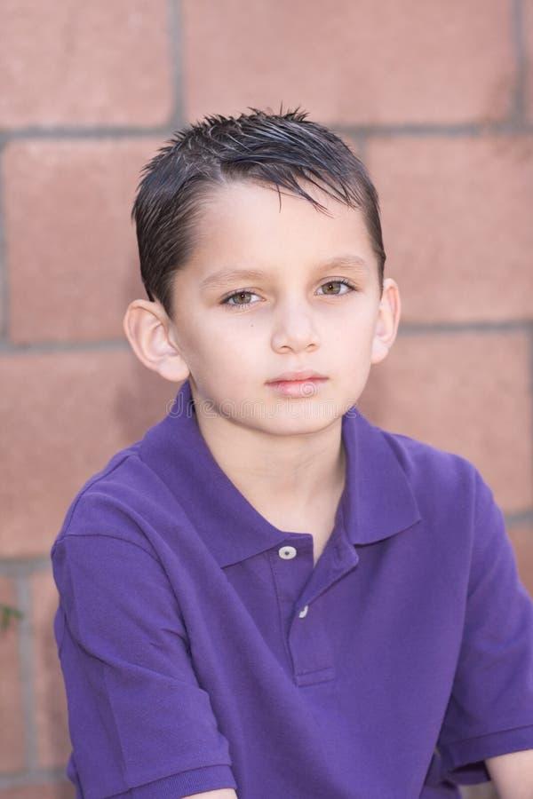 Junger biracial Junge des Portraits durch Backsteinmauer stockfoto