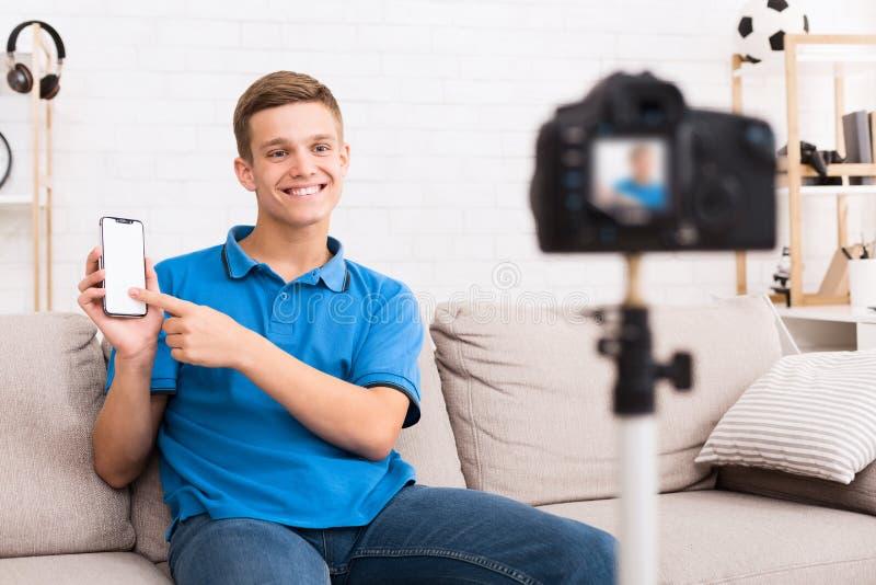 Junger Blogger, der auf Smartphone mit leerem Bildschirm zeigt stockbild
