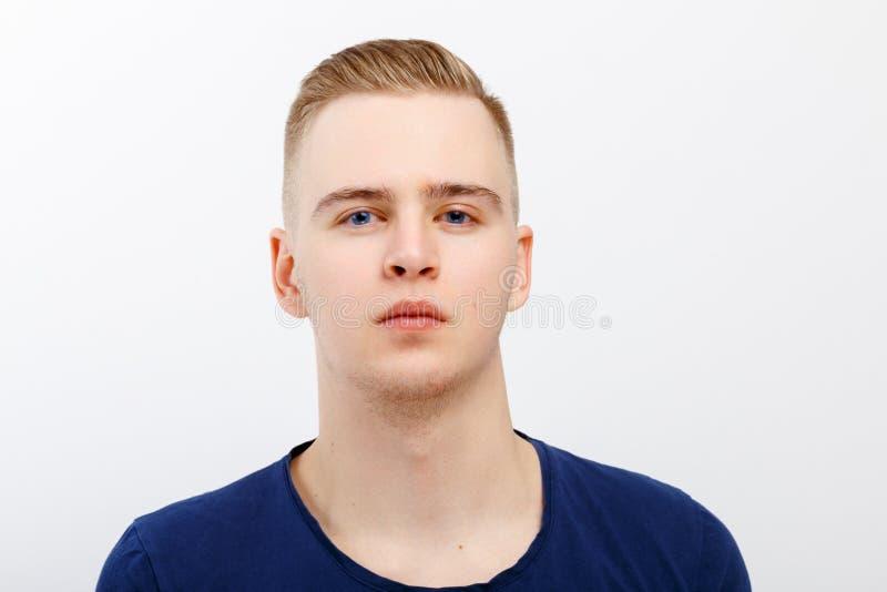 Junger blonder gutaussehender Mann in den blauen Hemdhaltungen lizenzfreie stockfotografie