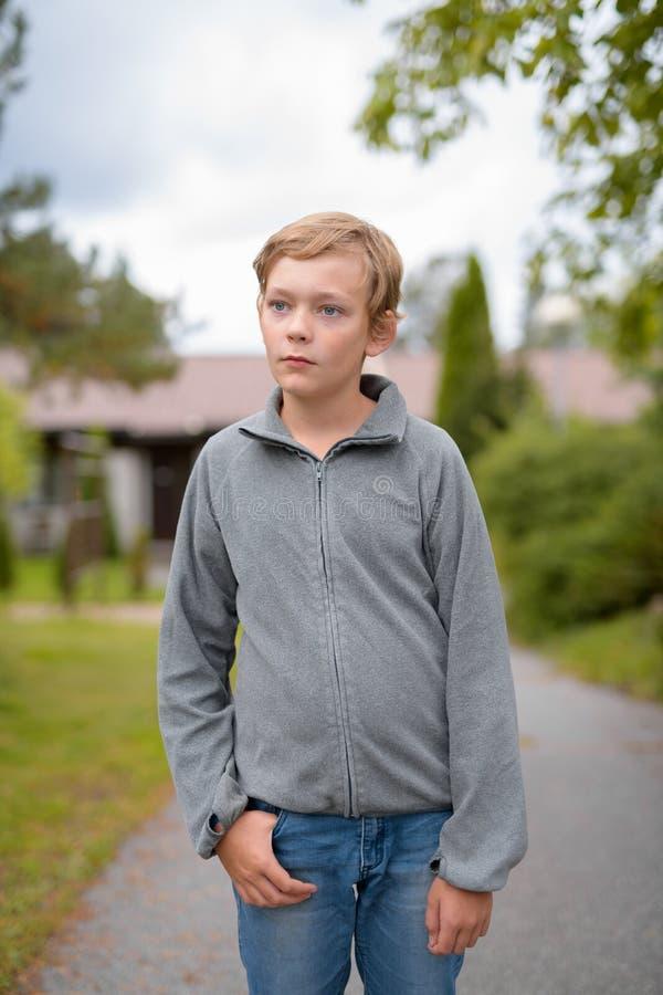 Junger blonder hübscher denkender Junge bei zu Hause stehen draußen lizenzfreie stockfotografie