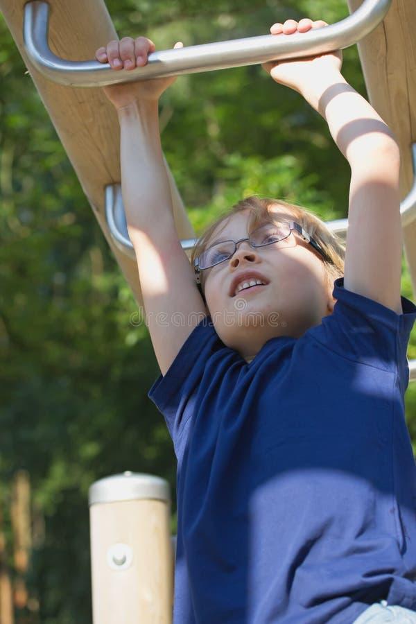 Junger blonder Junge spielt an den Kletterstangen. lizenzfreie stockbilder