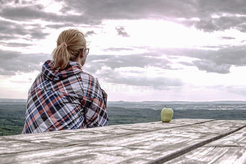 Junger blonder Mädchen Trekker, der am Holztisch stillsteht lizenzfreie stockfotos