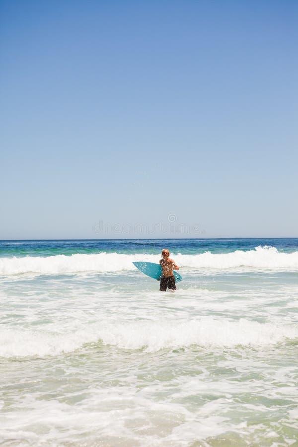 Junger blonder Mann, der zum Strand zurückkommt lizenzfreies stockbild