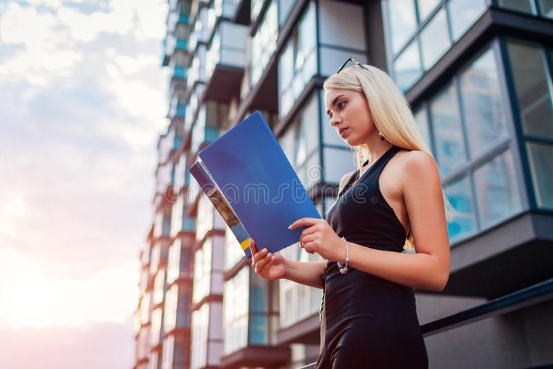 Junger blonder wirklicher eastate Mittel-Lesevertrag durch modernes mehrstöckiges Gebäude in der Stadt Geschäftsfrau überprüft Pr stockfoto