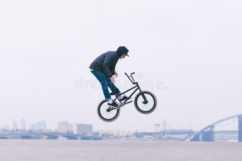 Junger BMX-Leser macht den Barzpin-Trick vor dem hintergrund der Stadtskyline lizenzfreie stockbilder