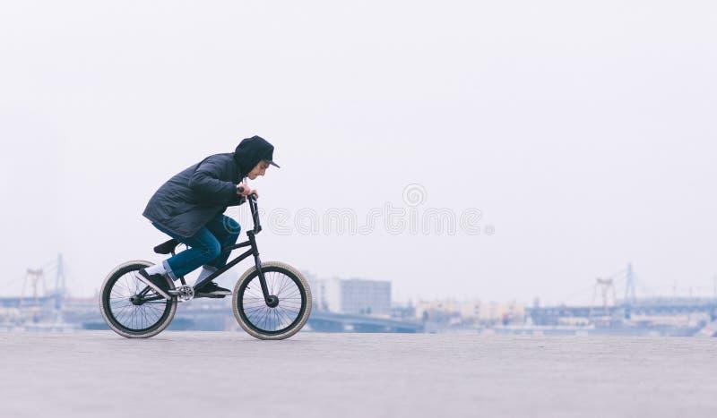 Junger BMX-Reiter, der ein Fahrrad auf einen unbedeutenden Stadthintergrund reitet BMX-Radfahrer wird einen Trick machen stockbild