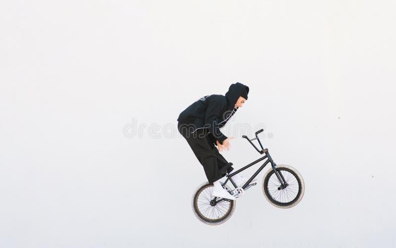 Junger Bmx-Reiter macht den barzpin Trick vor dem hintergrund der weißen Wand BMX-Konzept lizenzfreie stockbilder