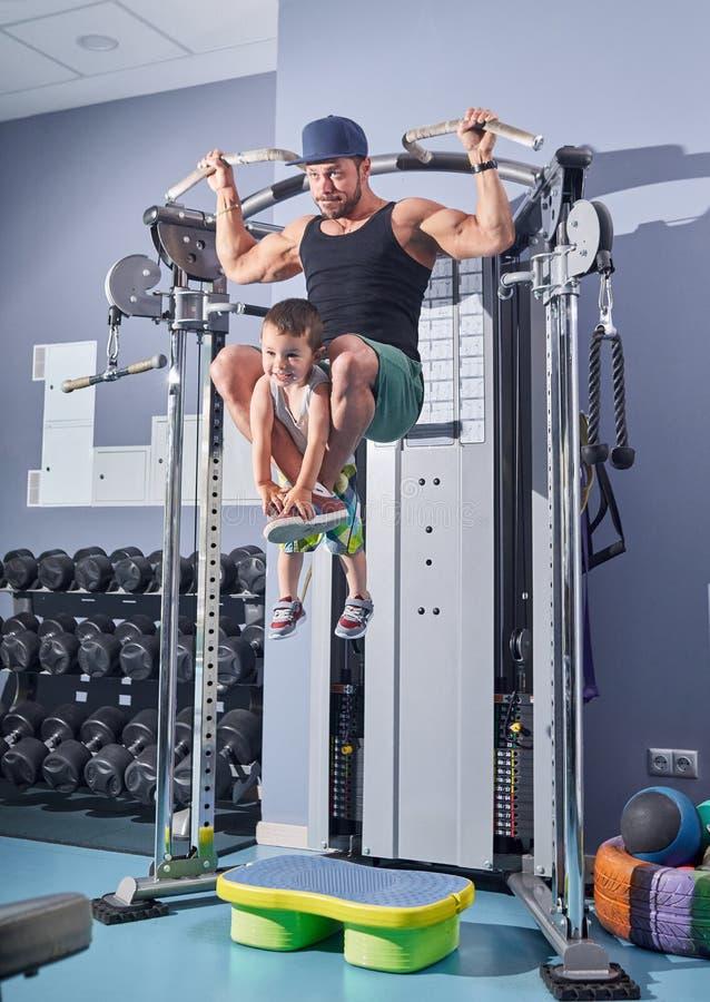 Junger Bodybuilder, der in die Turnhalle hält kleinen Sohn mit seinen Beinen anhebt stockbild