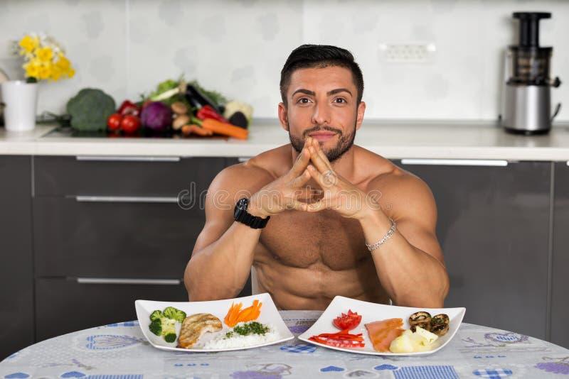 Junger Bodybuilder in der Küche lizenzfreie stockbilder