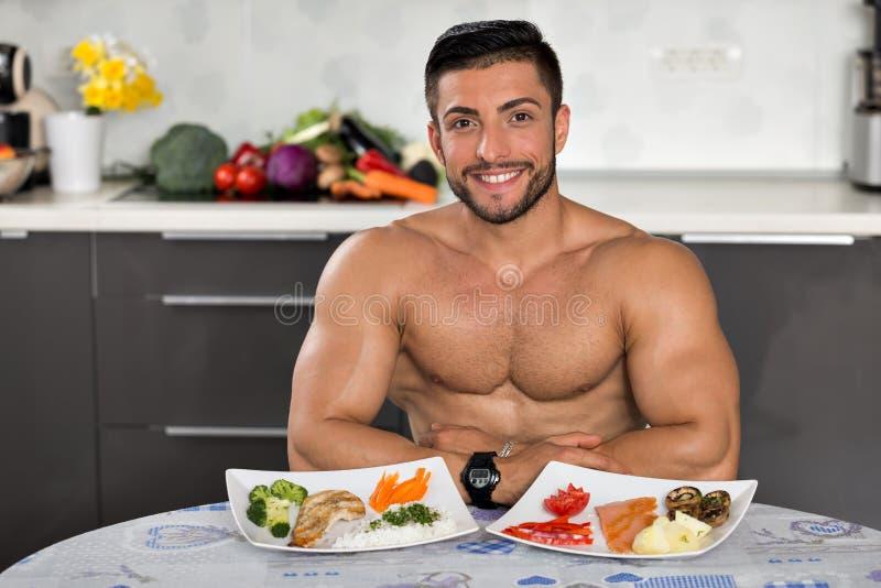 Junger Bodybuilder in der Küche stockfoto