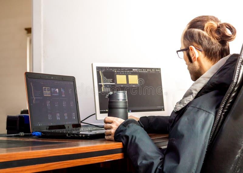 Junger Brünettegeschäftsmann, der Thermosflasche mit dem Morgenkaffee arbeitet im Büro hält stockbild