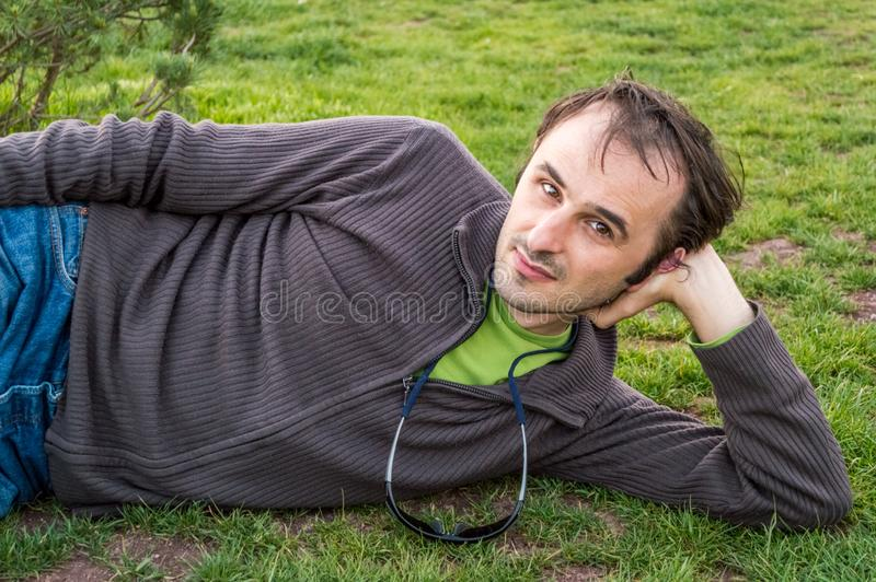 Junger Brünettemann in der Freizeitbekleidung, die auf Gras im Park sich entspannt stockfoto