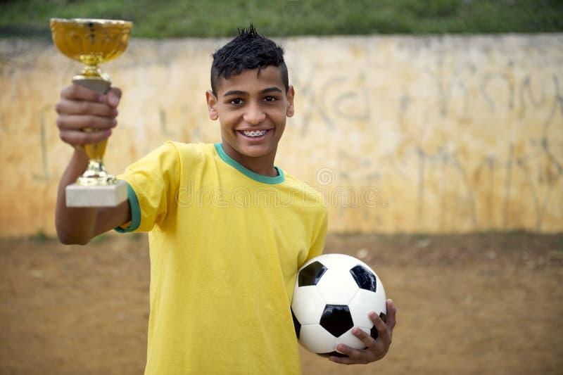 Junger brasilianischer Fußball-Fußball-Spieler, der Trophäe hält lizenzfreies stockbild