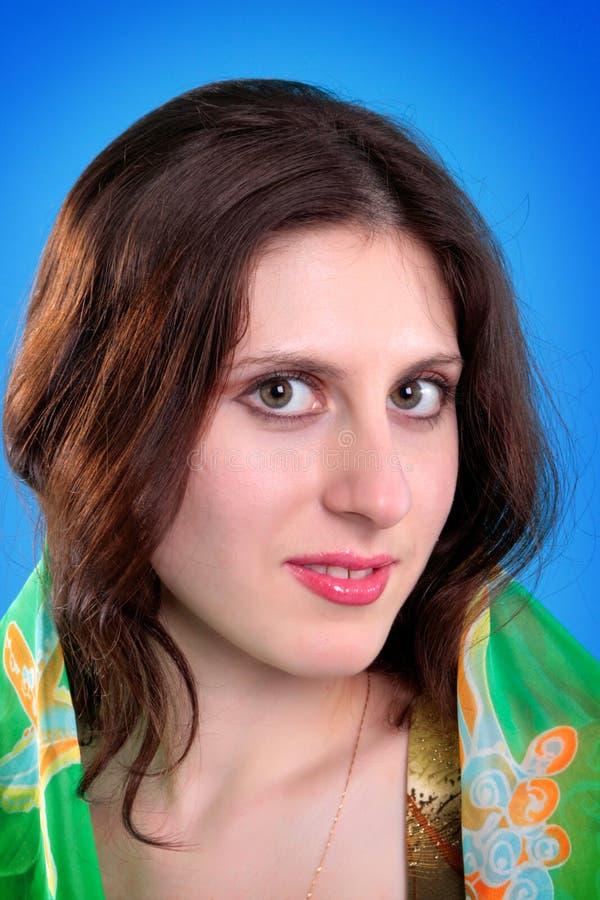 Junger Brunette auf einem blauen Hintergrund stockfotografie