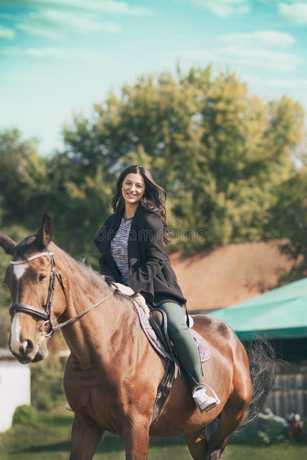 Junger Brunette auf einem Pferderuecken, Lebensstil auf Landschaft stockfoto
