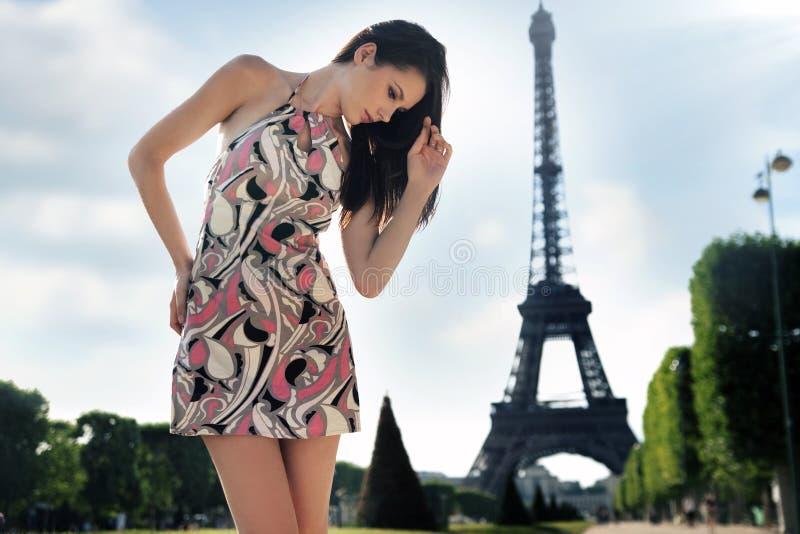 Junger Brunette, der über Eiffelturmhintergrund aufwirft stockbilder