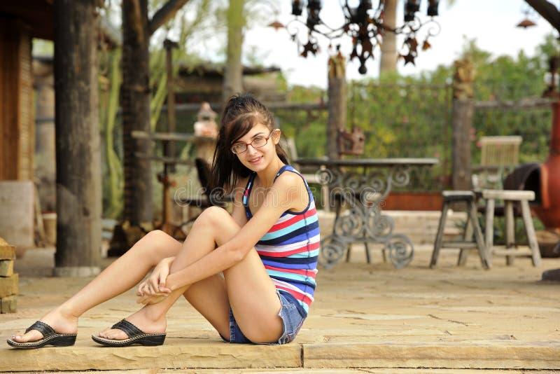 Junger Brunette, der auf Steinpatio sitzt stockfoto