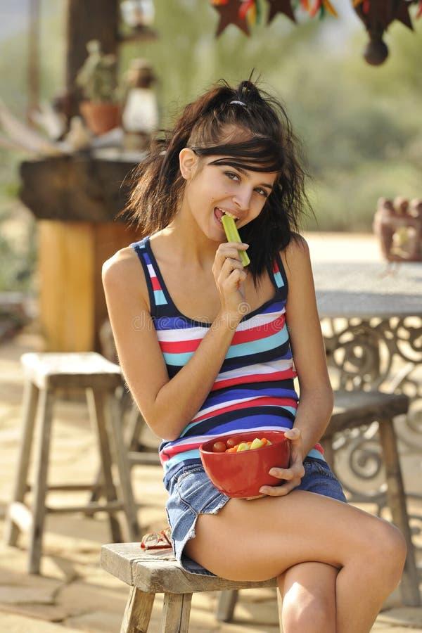Junger Brunette, der gesunden Imbiß isst lizenzfreies stockbild