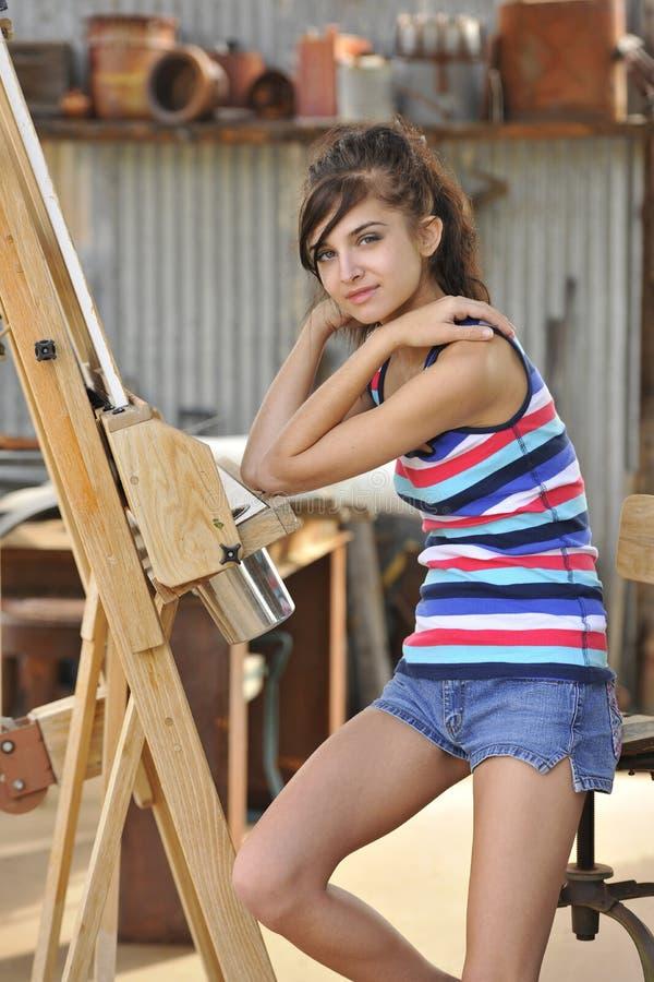 Junger Brunette, der am Maler-Gestell sitzt stockfoto