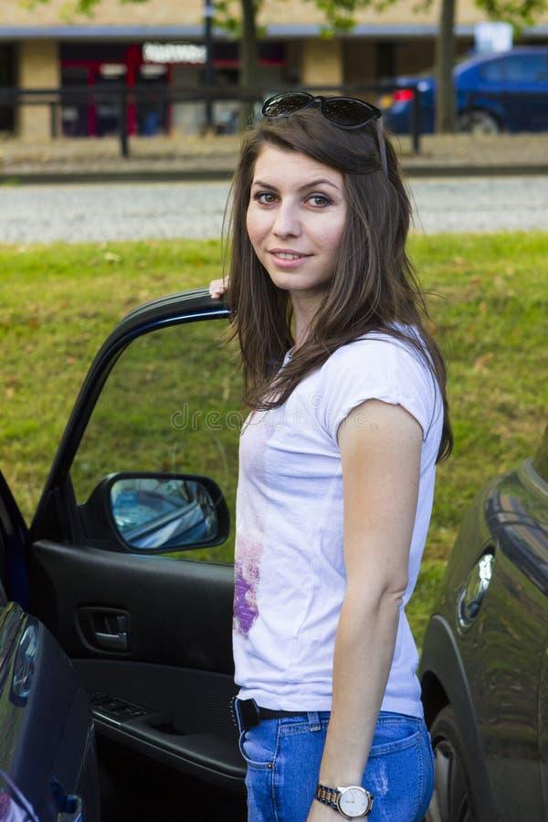 Junger Brunette, der nahe Auto aufwirft lizenzfreie stockfotografie