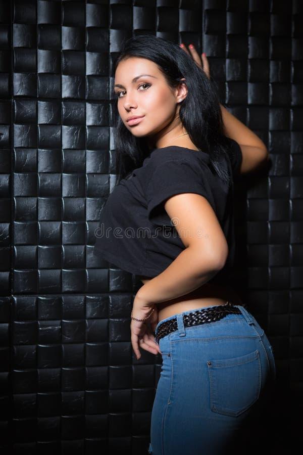 Junger Brunette, der schwarzes T-Shirt und Blue Jeans trägt lizenzfreie stockbilder