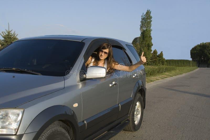Junger Brunette, der silbernes Auto antreibt stockfoto