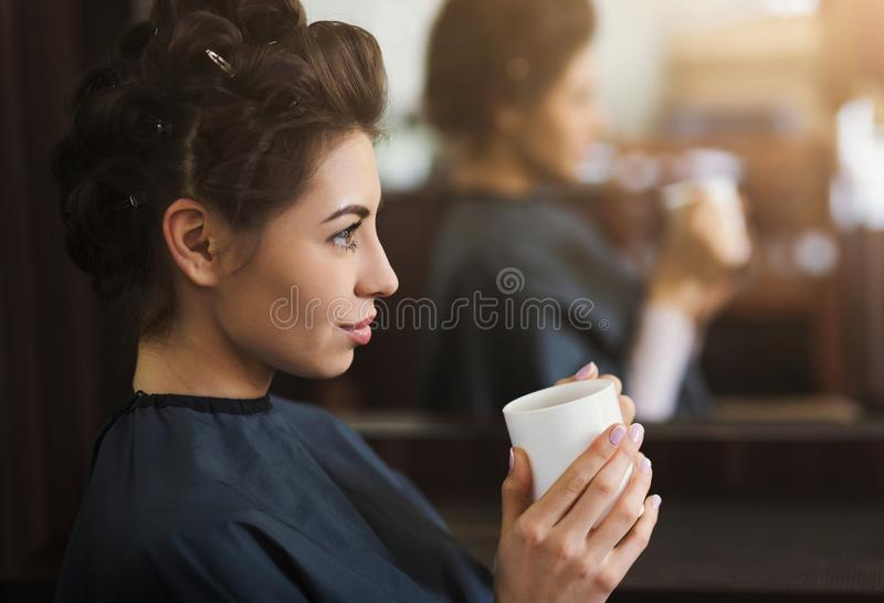Junger Brunette, der Tasse Kaffee am Schönheitssalon hat lizenzfreies stockbild