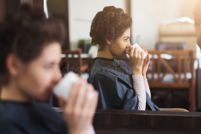 Junger Brunette, der Tasse Kaffee am Schönheitssalon hat stockfotografie