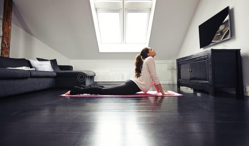 Junger Brunette, der zu Hause auf Boden trainiert lizenzfreie stockbilder