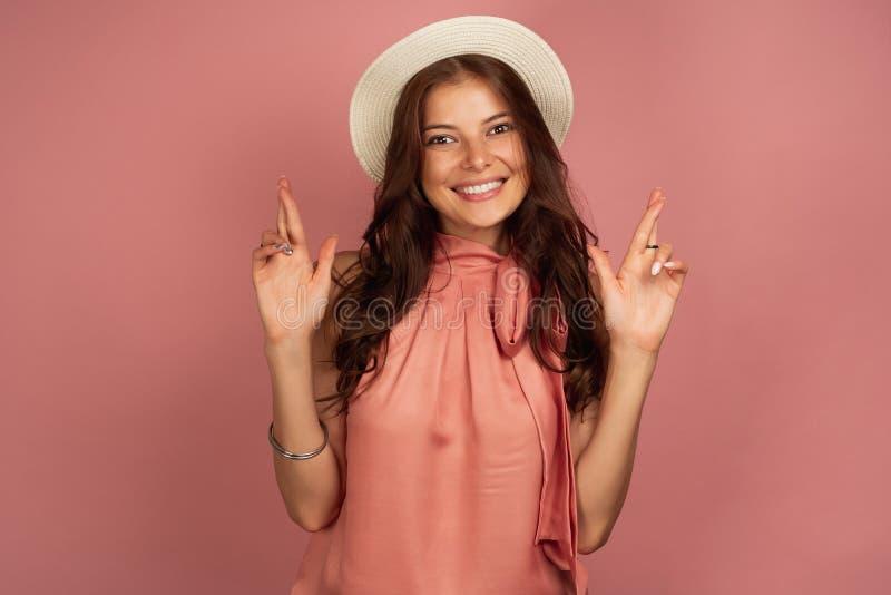 Junger Brunette in einem Hut kreuzt ihre Finger für Glück mit einem Lächeln, rosa Hintergrund stockfotos