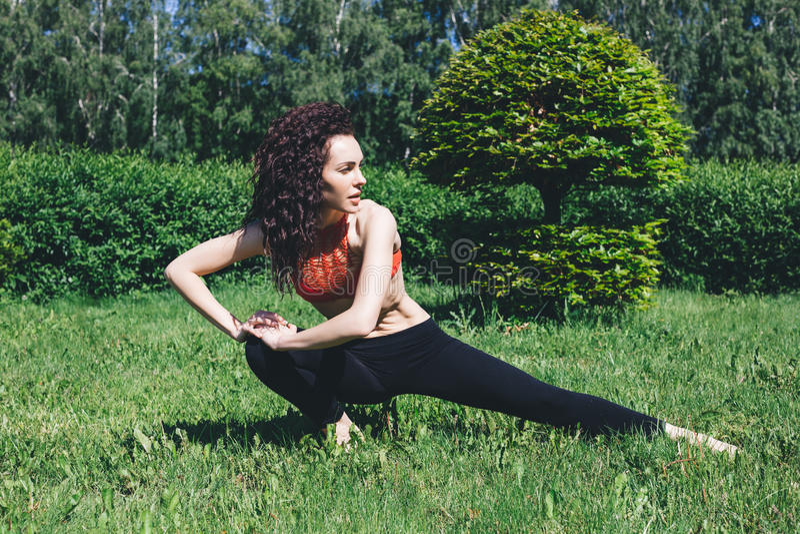 Junger Brunette macht athletisch auf dem Gras lizenzfreie stockbilder