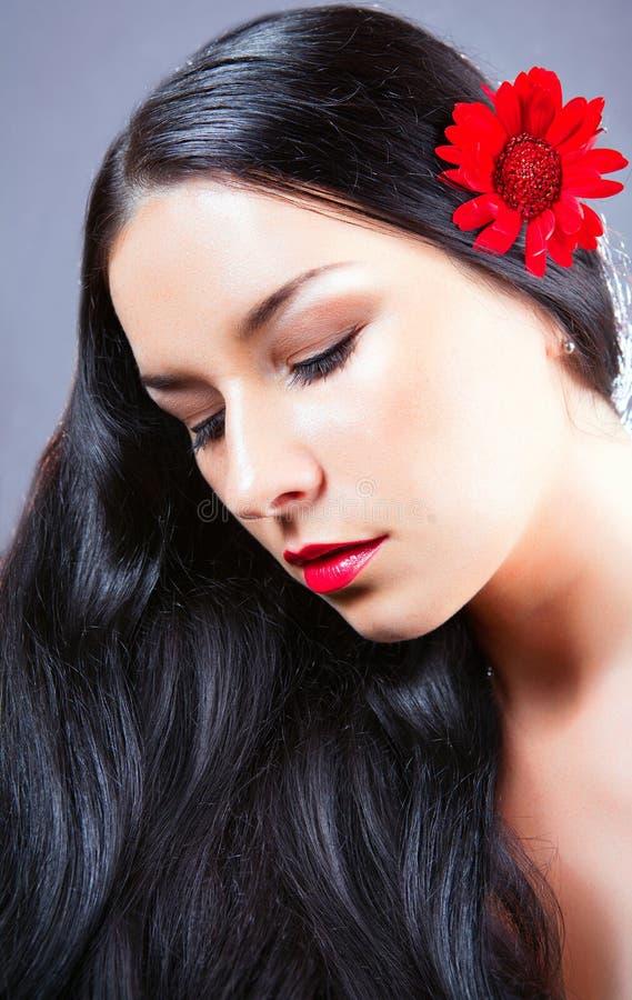 Junger Brunette mit roter Blume in ihrem Haar. lizenzfreie stockfotografie
