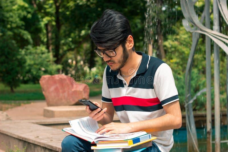 Junger Brunettestudentenjunge mit Büchern in den Händen unter Verwendung eines Handys stockbild