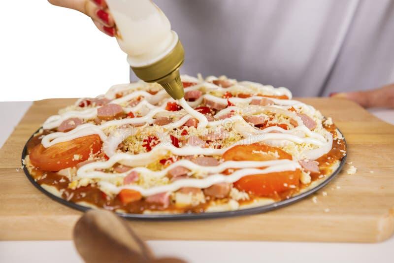 Junger Chef, der Majonäse auf einer Pizza hinzufügt lizenzfreies stockbild