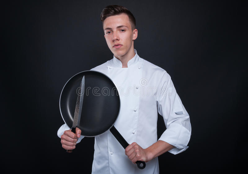 Junger Chef oder Koch mit Messer und Wanne stockfotos