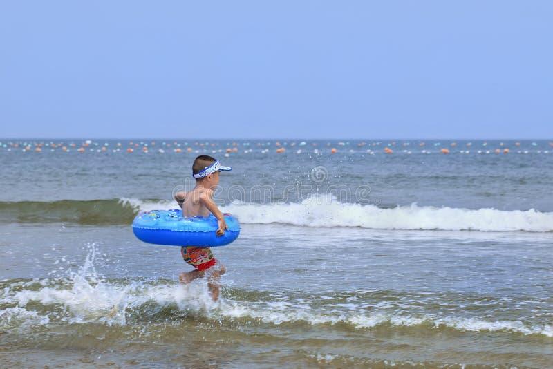 Junger chinesischer Junge hetzt in das Meer, Yantai, China stockfotos