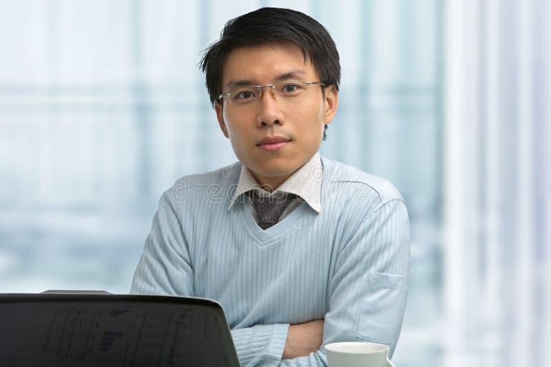 Junger chinesischer Mann, der im Büro arbeitet lizenzfreies stockbild