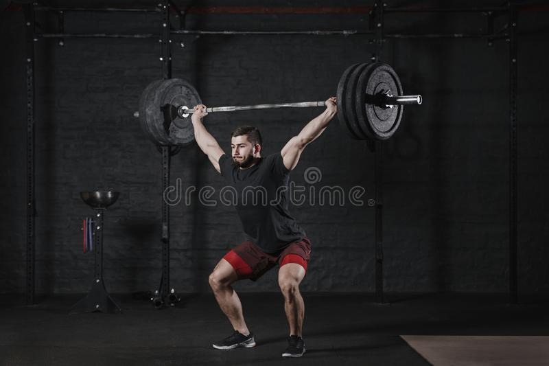 Junger crossfit Athlet anhebender Barbell oben an der Turnhalle Mann, der Funktionsausbildungspowerlifting Trainingsübungen übt stockbild