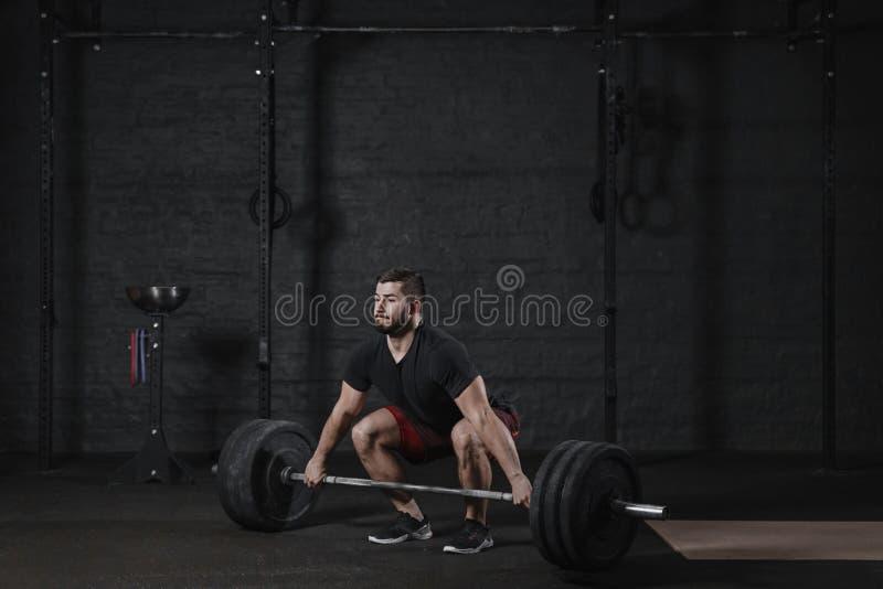 Junger crossfit Athlet, der deadlift Übung mit schwerem Barbell an der Turnhalle tut Mann, der Funktionsausbildungspowerlifting T lizenzfreies stockbild