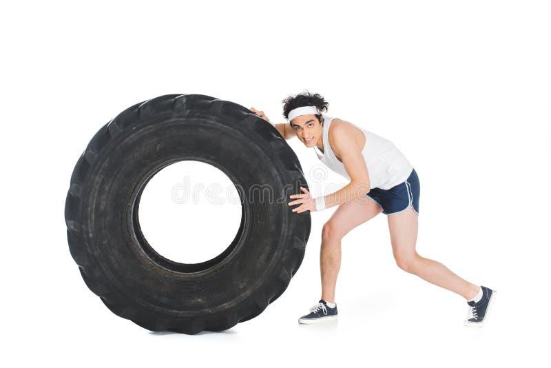 Junger dünner Sportler, der Reifen des Rades drückt lizenzfreies stockbild