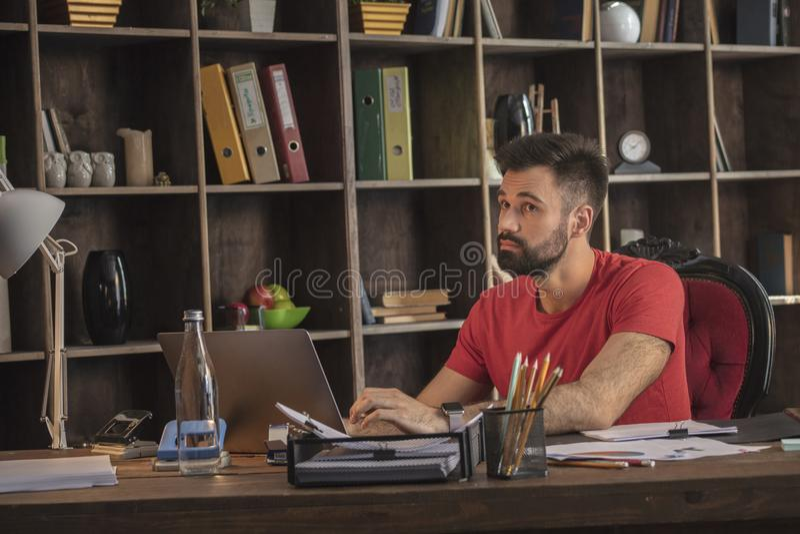Junger denkender Geschäftsmann beim Arbeiten mit Notizbuch auf welchem folgenden Projekt lizenzfreies stockfoto
