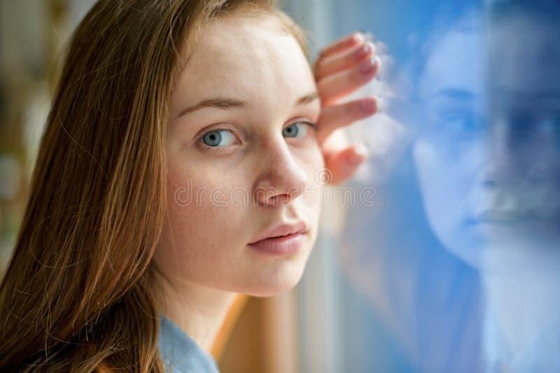 Junger deprimierter einsamer weiblicher Student, der ein Fenster an ihrer Schule, die Kamera betrachtend bereitsteht Einschüchter lizenzfreies stockfoto