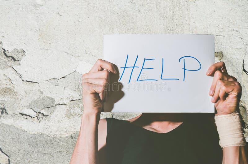 Junger deprimierter obdachloser Mann mit Verband auf seiner Hand vom Selbstmordversuchsholding-Hilfszeichen geschrieben auf Papie stockfotografie